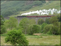 Glenfinnan monument, with the Jacobite steam train going across.  The viaduct was used to film scenes for the Harry Potter films